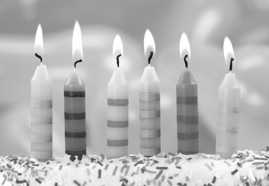 Six birthday candles on a colorful background